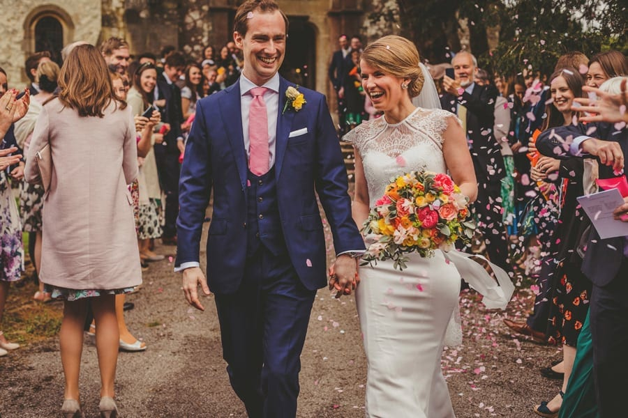 The bride and groom laugh with each other as confetti falls all around them outside the church