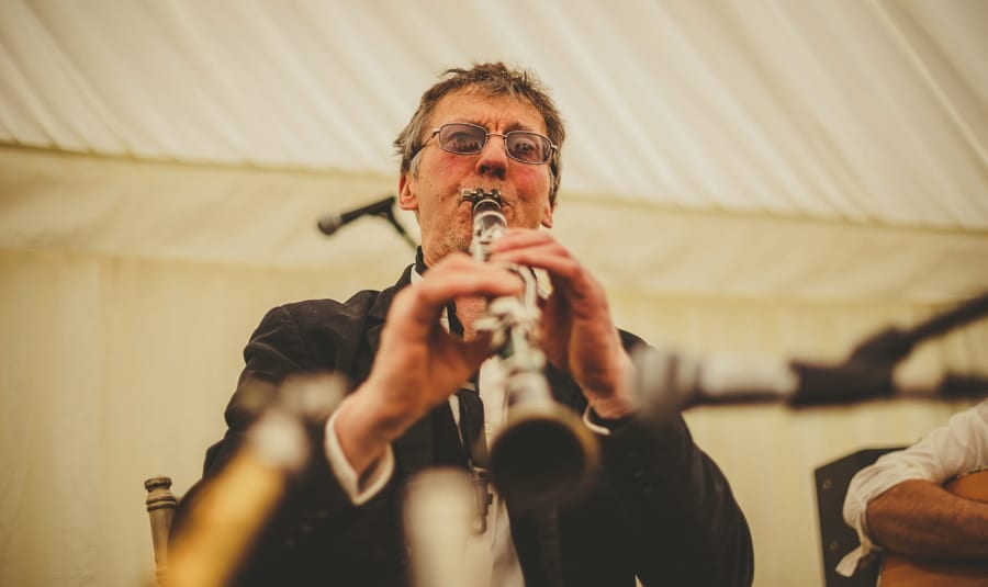 A member of the wedding band plays on stage in the marquee