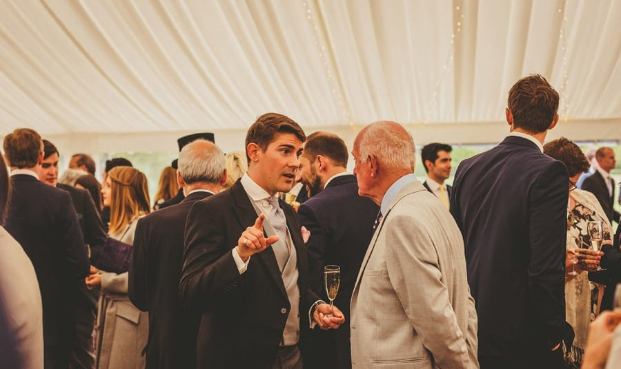 A wedding guest chats with a friend in the marquee