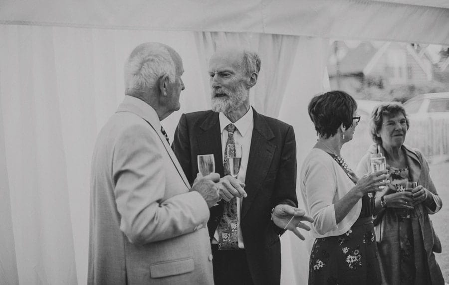 A wedding guest talks to a family member as they hold champagne flutes