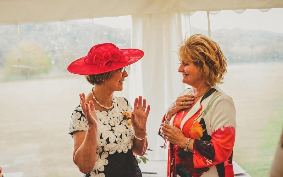 The brides mother talks with a friend in the marquee