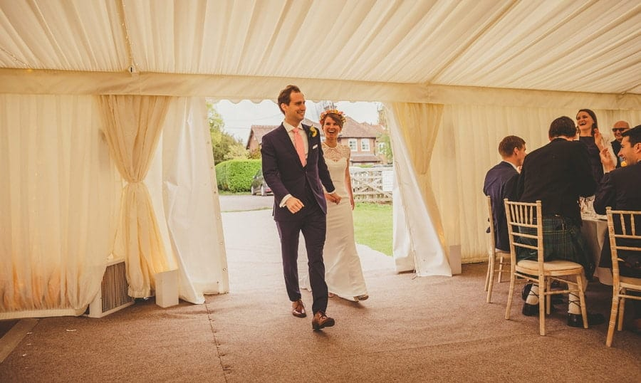 The bride and groom enter the marquee holding hands