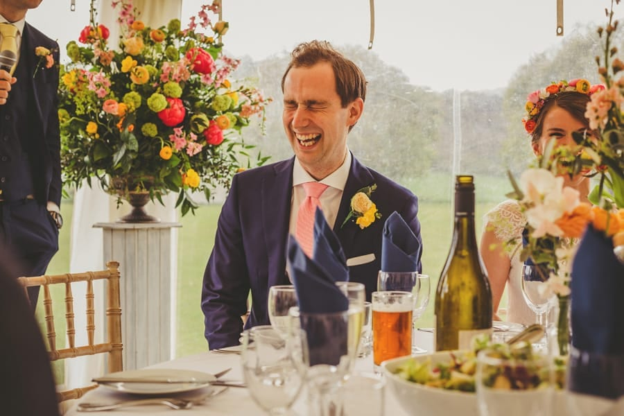 The groom sits at the wedding table and laughs