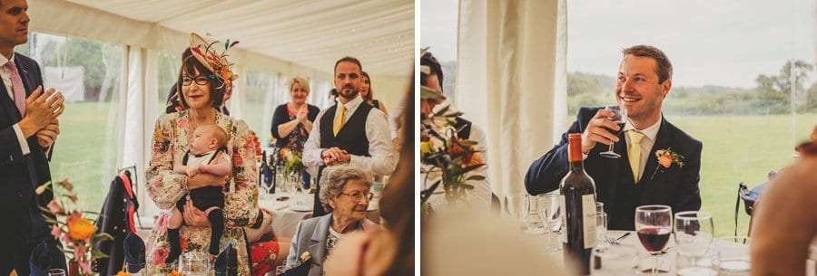 An usher listens to the wedding speeches sat at the table in the marquee