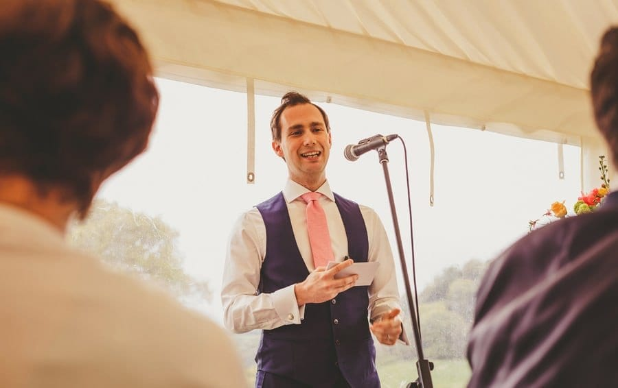 The groom stands in front of a microphone and delivers his speech in the marquee