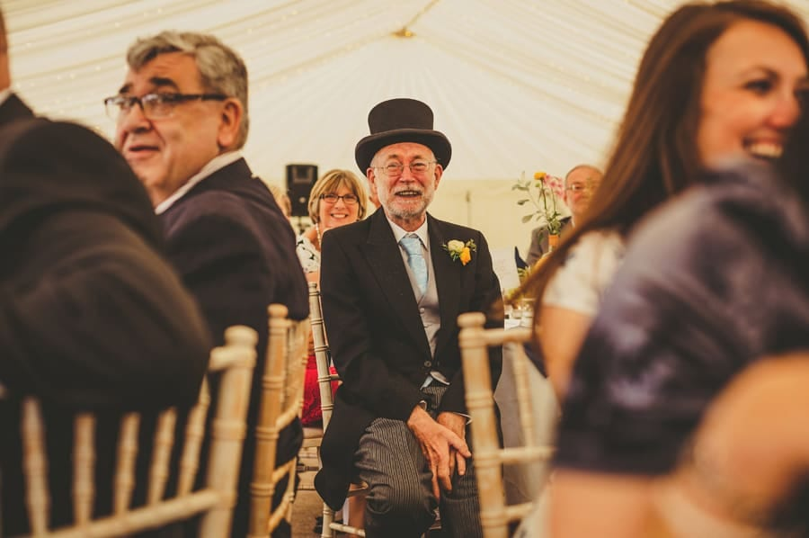 The brides father sits at a table and listens to the speeches in the marquee