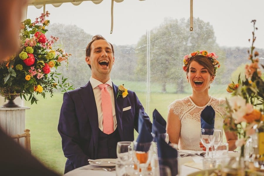 The bride and groom sit next to each other and laugh at the best mans wedding speech