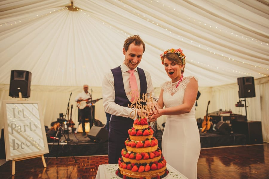 The bride and groom cut the wedding cake on the dancefloor in the marquee