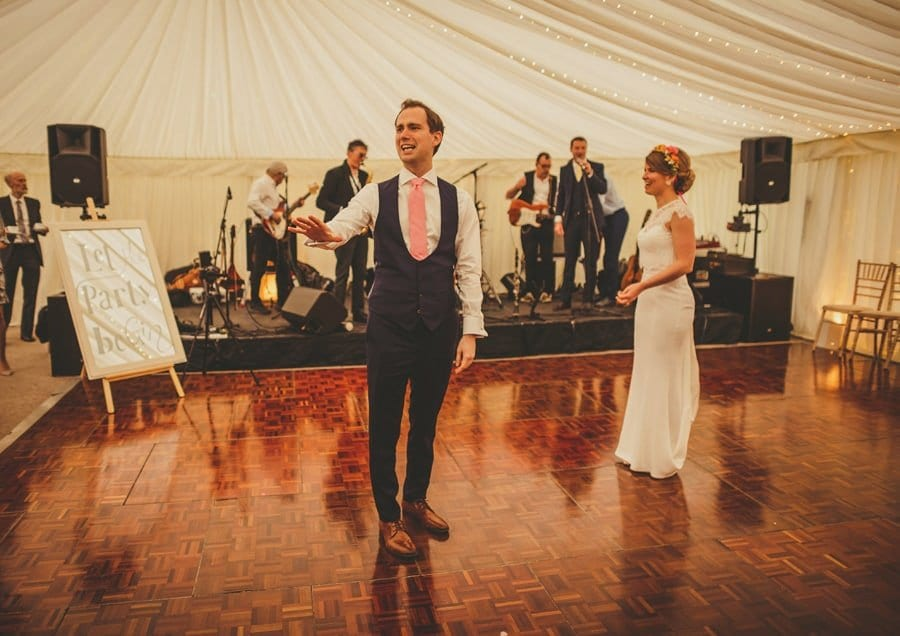The groom talks to wedding guests on the dancefloor in the marquee