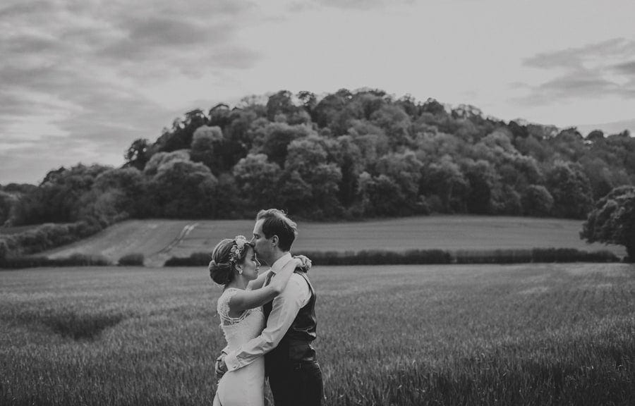 The groom kisses the bride on the forehead in a field