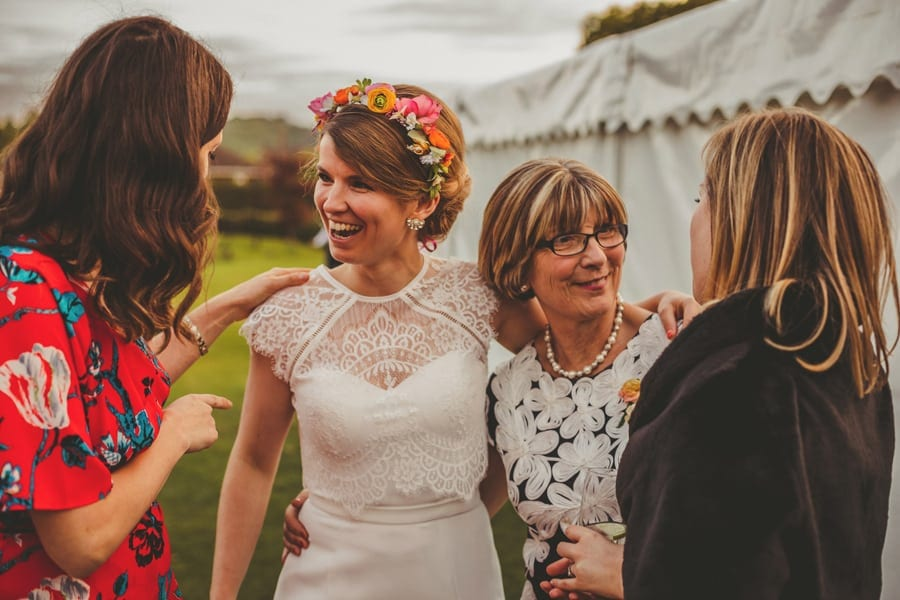 The bride stands and chats to her family outside the wedding marquee in East Hampshire