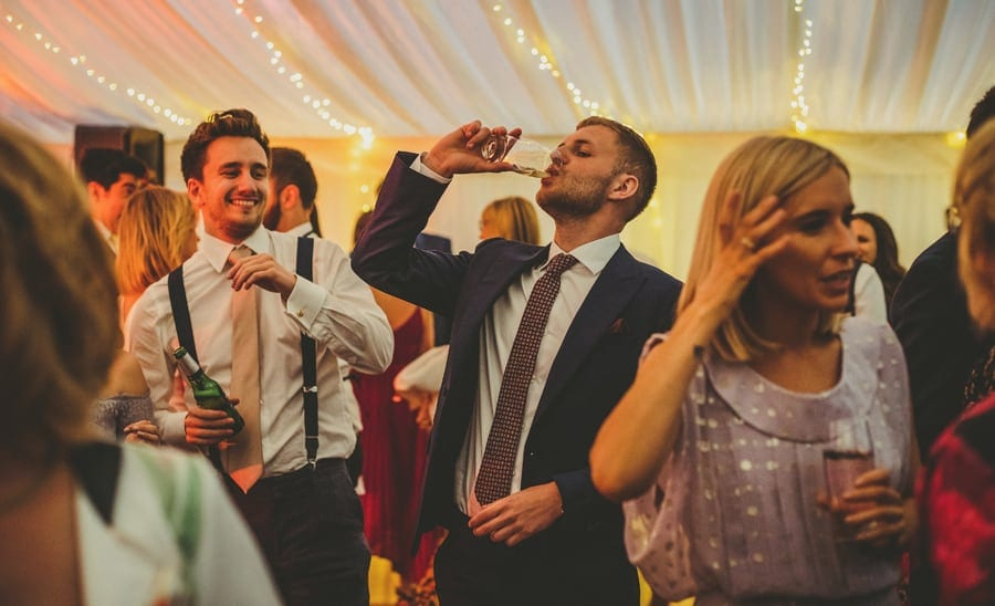 A wedding guest drinks a pint of beer on the dancefloor