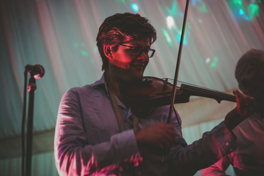 A member of the wedding band plays violin on stage