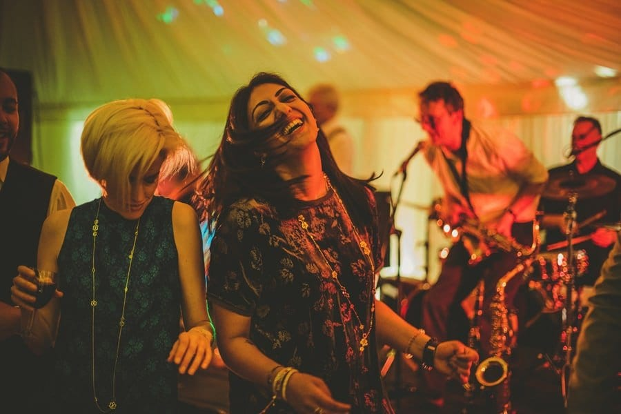 Two ladies dance next to each other in the marquee