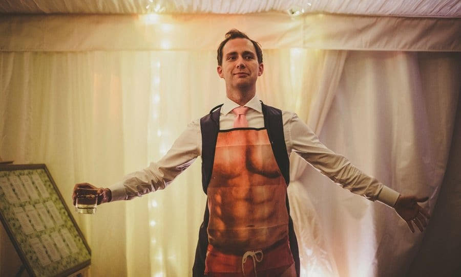 The groom stands on the edge of the dancefloor in the marquee holding a glass and wearing an apron