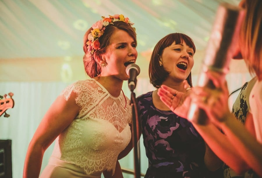 The bride sings into a microphone with her friend on stage