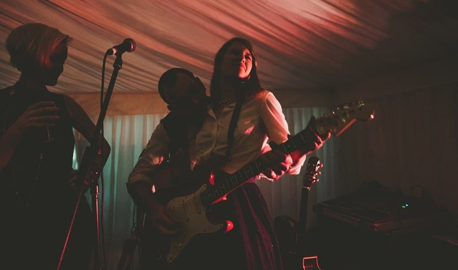 A wedding guest plays guitar on stage