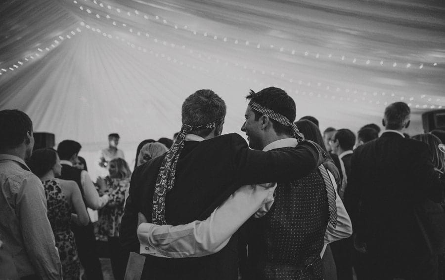 Wedding guests with ties wrapped around their heads put their arms around each other in the marquee