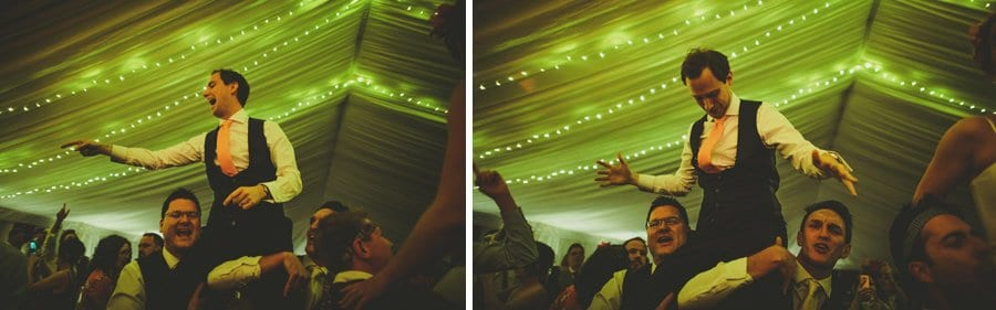 Wedding guests lift the groom onto their shoulders in the marquee