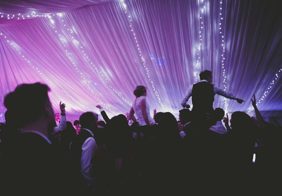 The bride and groom are lifted onto the wedding guests shoulders on the dancefloor of the marquee