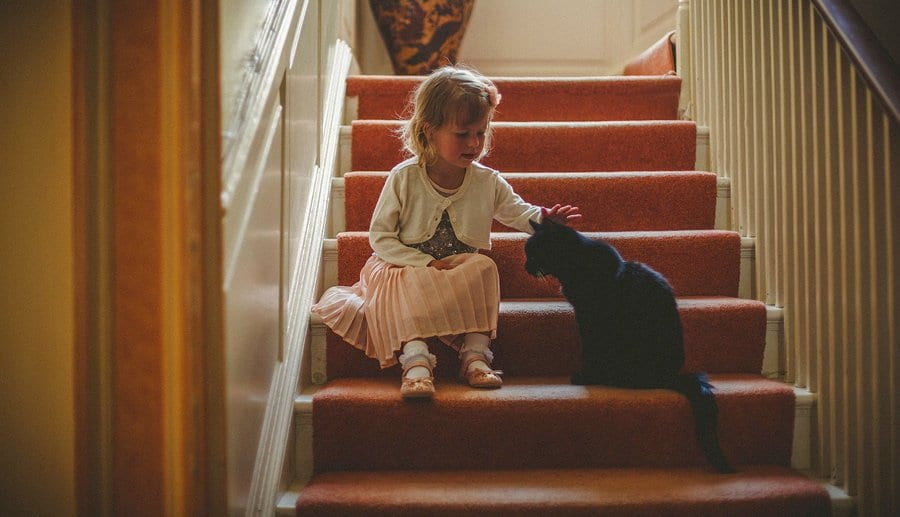 A little girl sits on the stairs and strokes a black cat