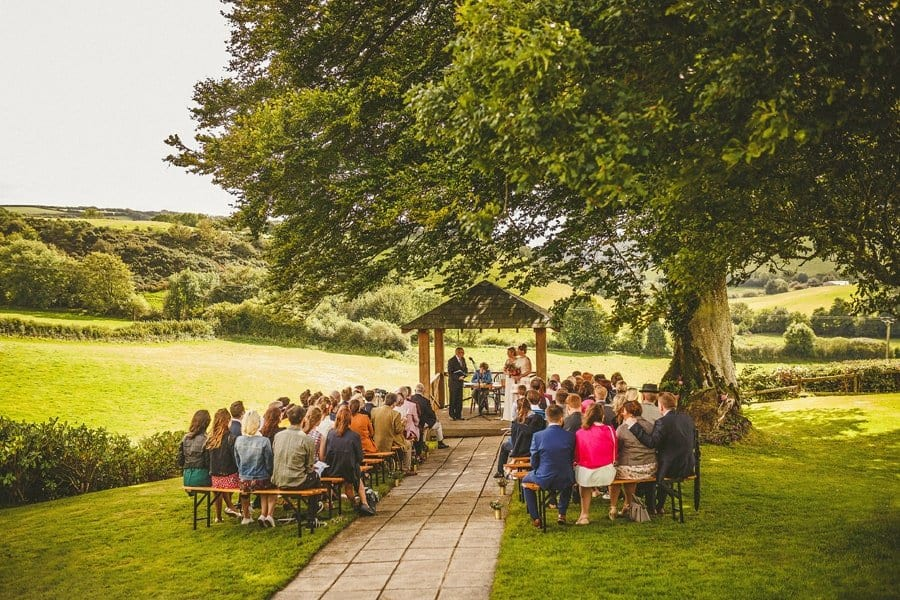 An outdoor wedding ceremony with wedding guests sat on long wooden benches in front of the bride and groom in the countryside