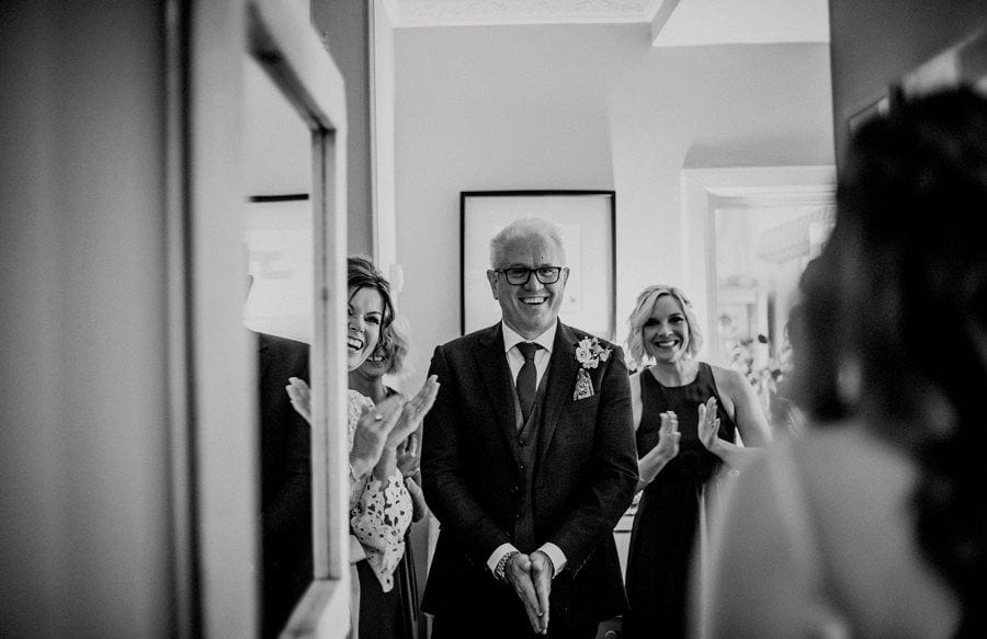 The bride's father and his family greet the bride as she walks towards them in her wedding dress