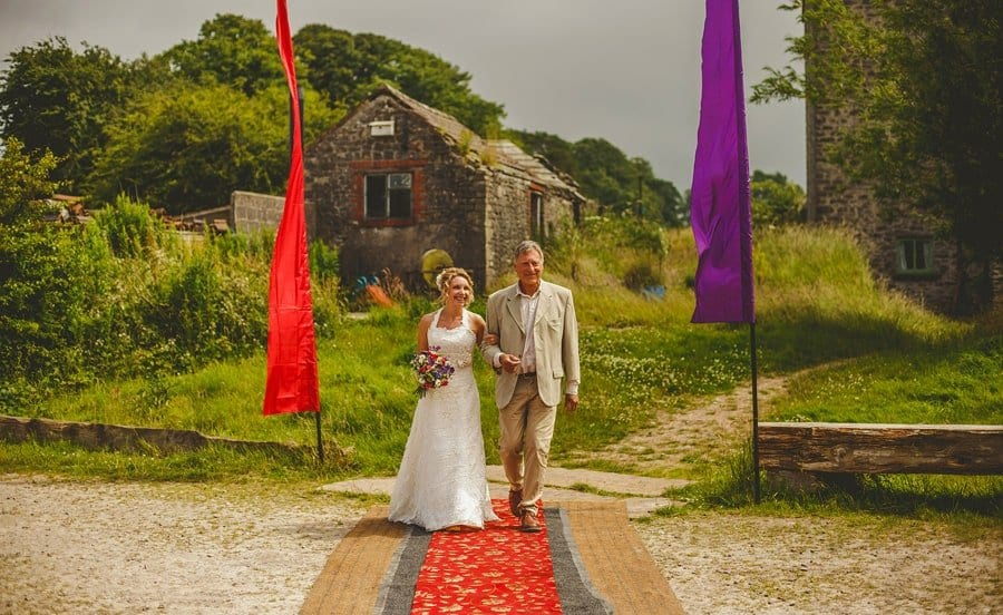 The bride holding her bouquet of flowers in her right hand and her father walk towards the outdoor wedding ceremony