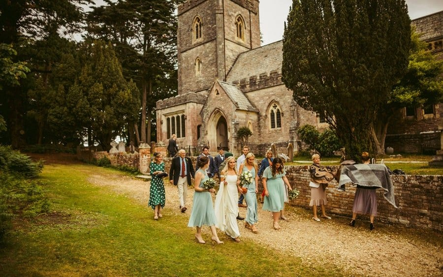The bride and her bridesmaids walk away from the Church after the wedding ceremony