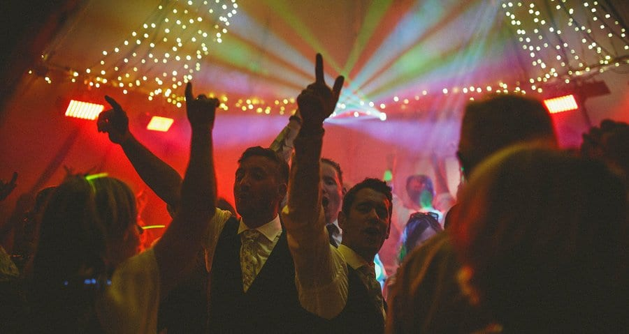 The groom and his friends on the dancefloor of the marquee raise their hands in the air