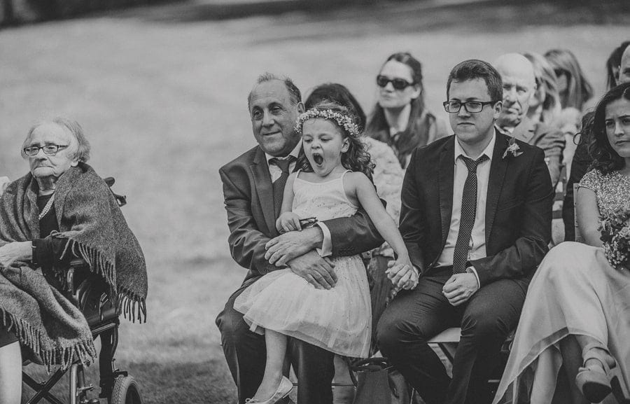 The flower girl yawns as she sits on her grandfathers lap