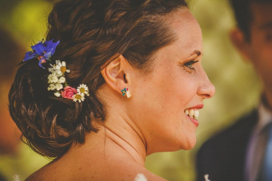 The bride turns around and smiles at the wedding guests during the outdoor ceremony at Longstowe Hall