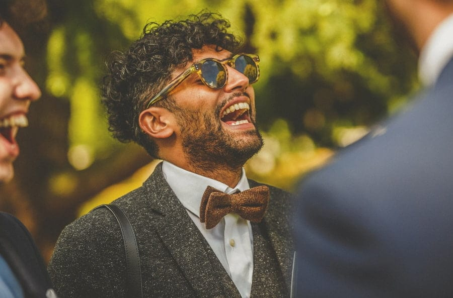 A wedding guest laughs at a comment made by an usher