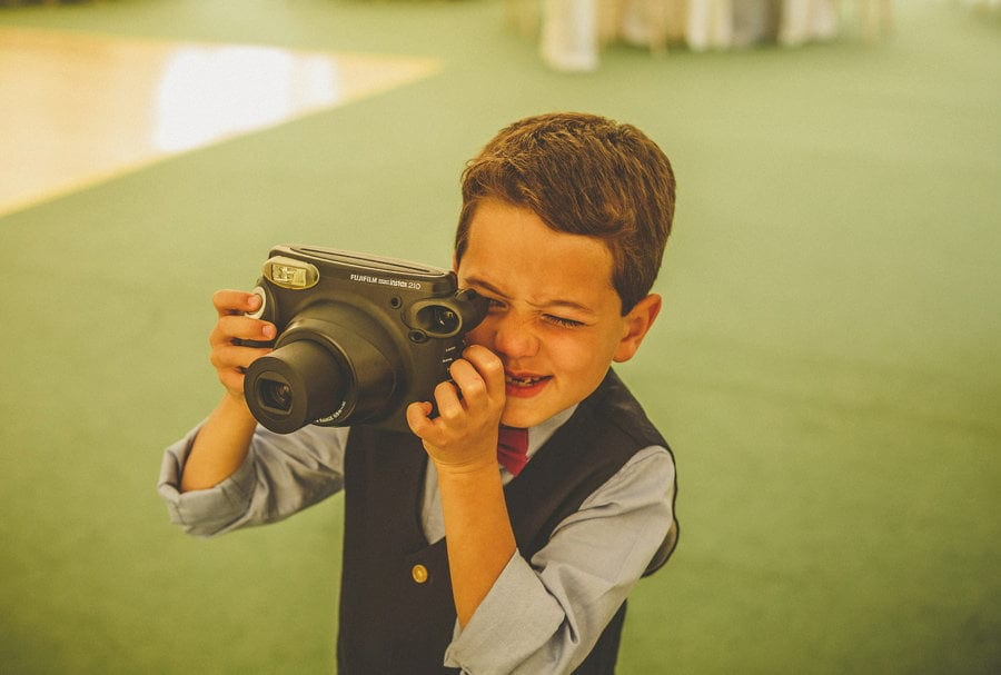 A boy takes a polaroid photograph in the marquee