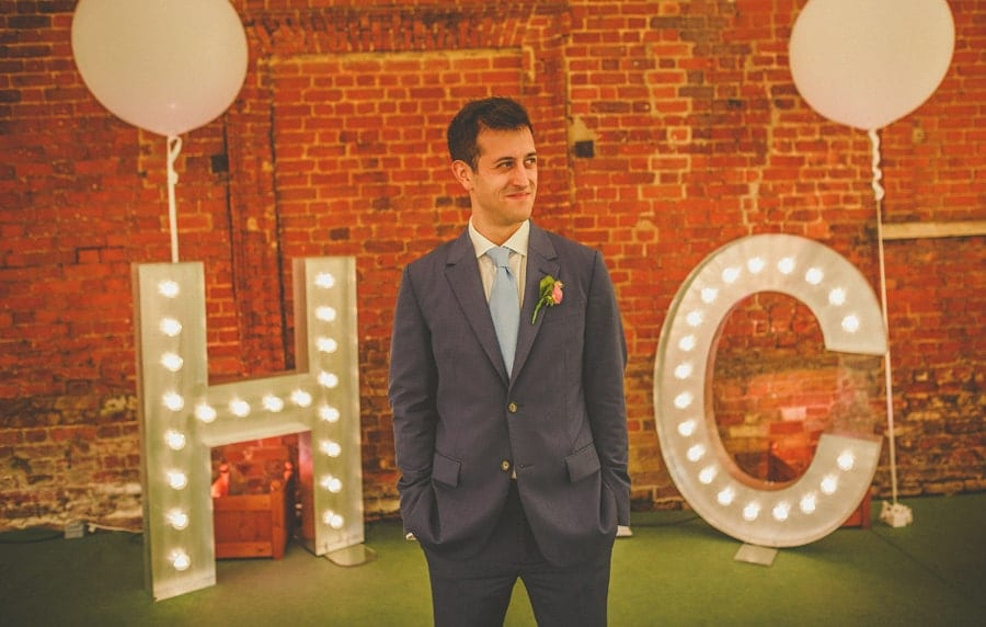 The groom poses for a photograph outside the marquee