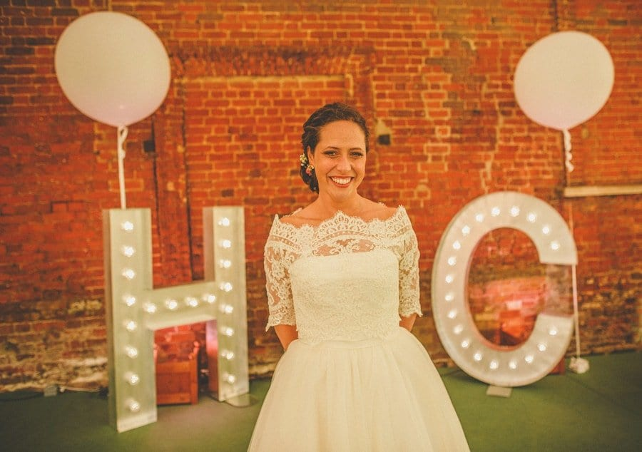 The bride poses for a photograph outside the marquee