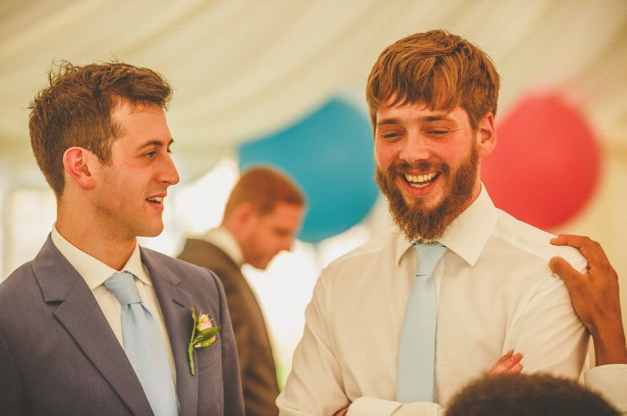 The groom and best man laugh and joke in the marquee