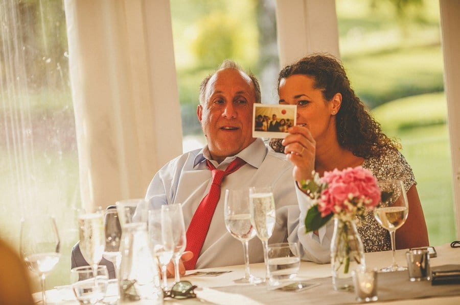 The grooms father shows the brides sister a photograph