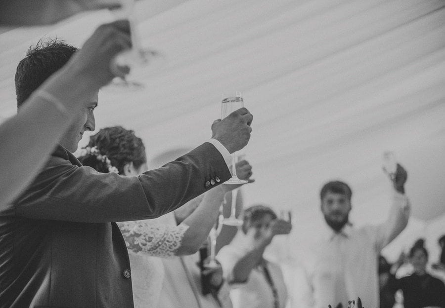 The bride and groom raise their glass to the wedding party in the marquee at Longstowe Hall