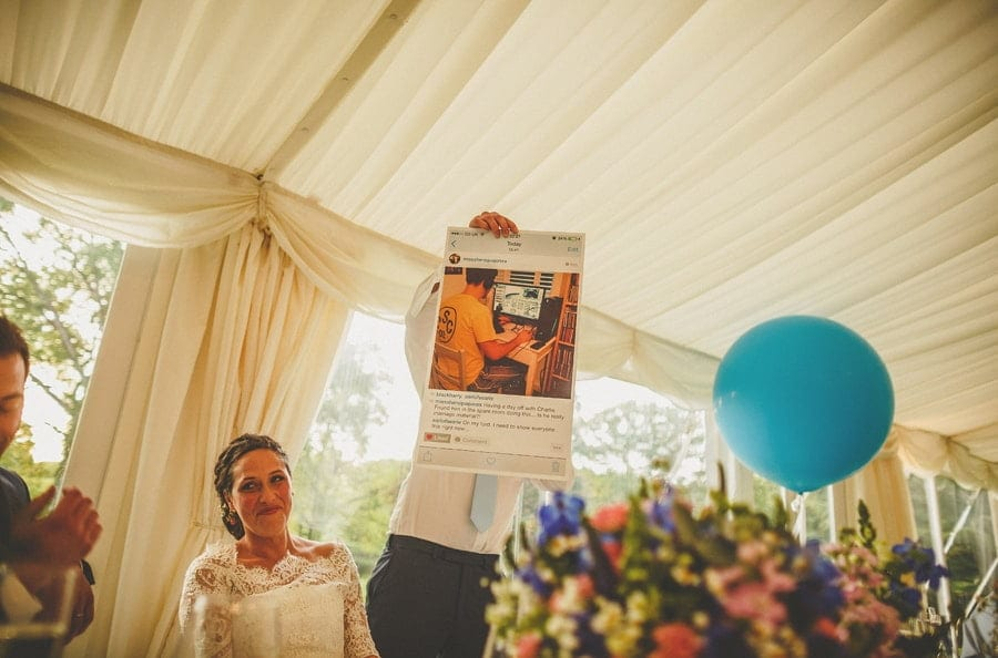 The best man holds up a photograph of the groom