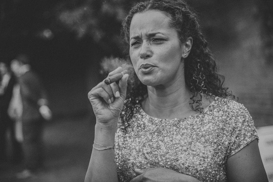 The bridesmaid exhales her cigar in the garden
