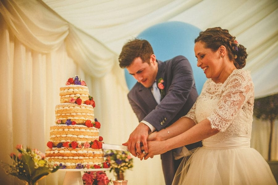 The bride and groom cut the cake in the marquee at Longstowe Hall