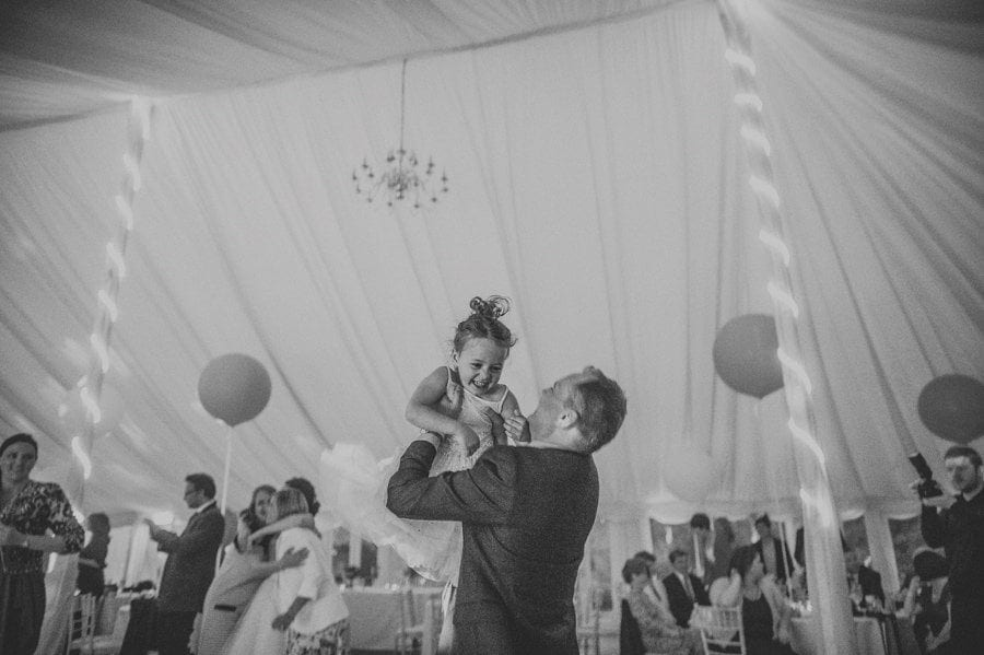 One of the wedding guests lifts up a flower girl on the dancefloor in the marquee