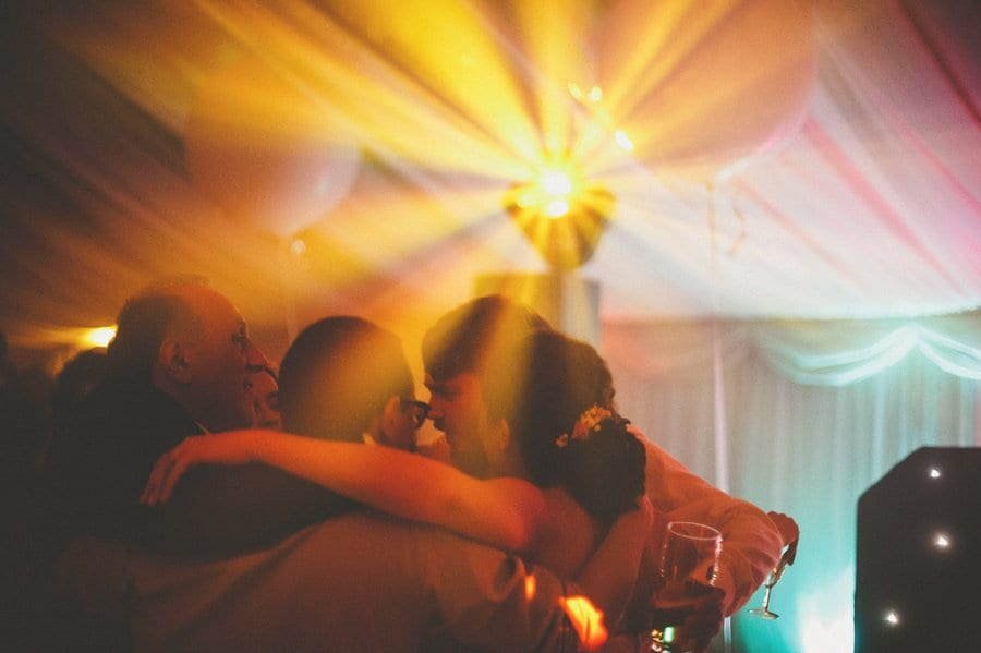 The grooms father embraces friends and family on the dancefloor