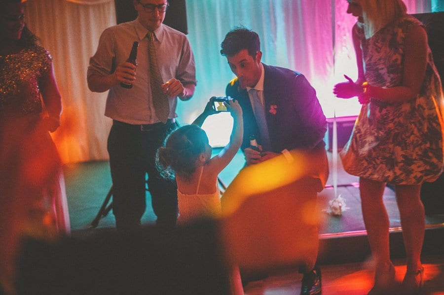 The groom poses for a photograph from one of the flower girls on the dancefloor