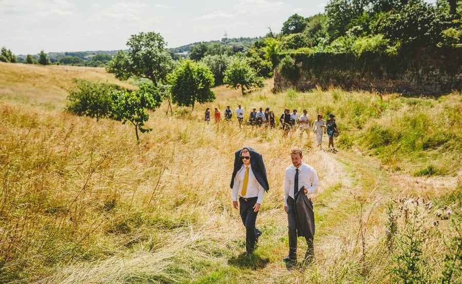 Wedding guests walking through a field towards the wedding venue