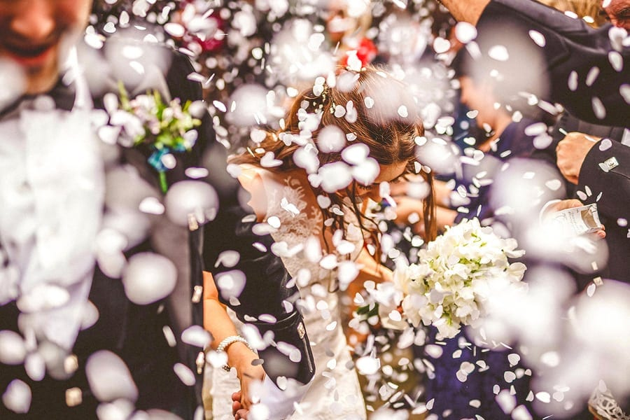 Confetti fall onto the bride and groom