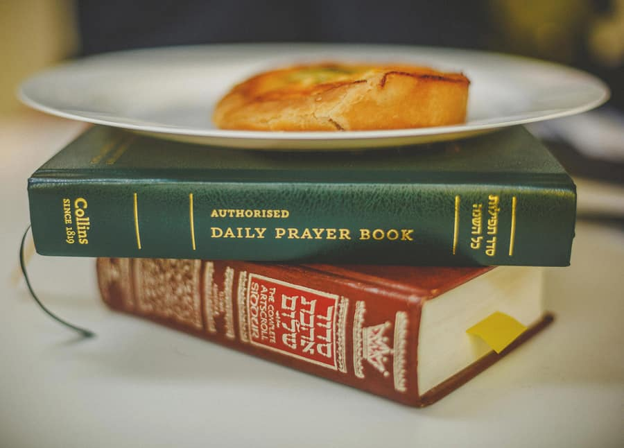 A jewish daily prayer book lies on top of another book with a plate and a pastry on top of them