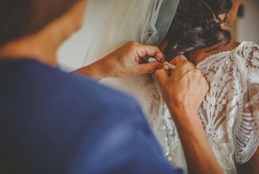 The mother of the bride fastens a button on the back of the brides dress