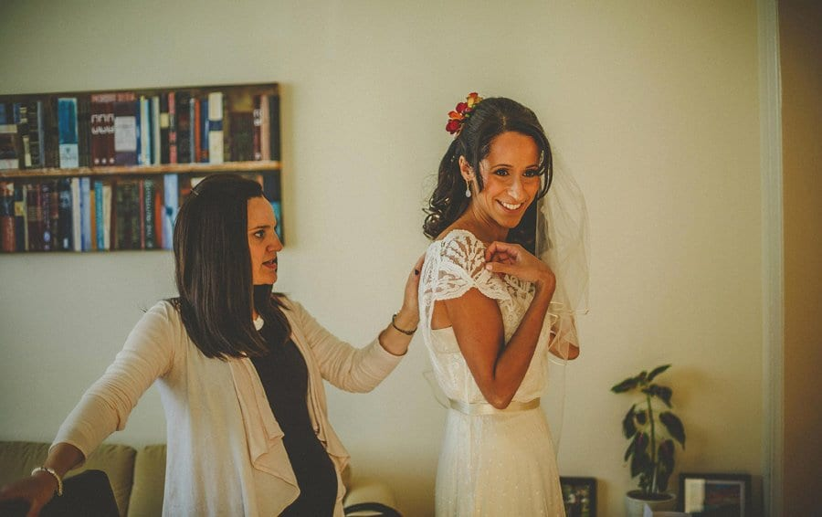 The bride smiles as she listens to a friend share a joke with her